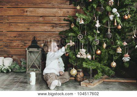 3 years old child celebrating holidays near Christmas tree, farm house design