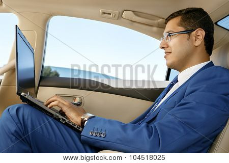 Businessman working in the back-seat of a car