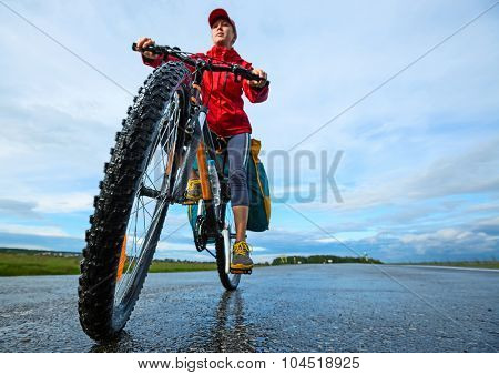 Young lady rides a bike with backpack on a wet asphalt road. Focus on the wheel.