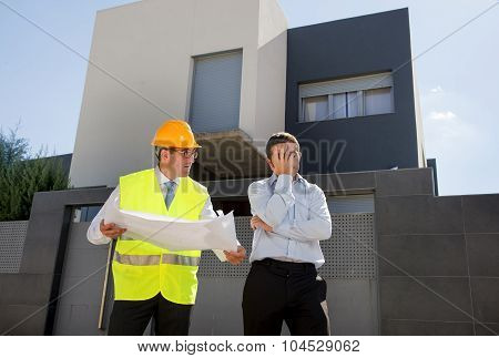 Unhappy Customer In Stress And Constructor Foreman Worker With Helmet And Vest Arguing Outdoors