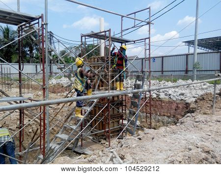 Construction workers fabricating timber column formwork at the construction site