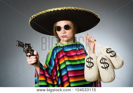 Girl in mexican poncho holding handgun and money sacks against gray