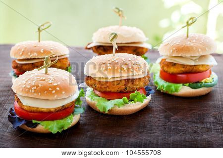 Mini Chicken Burgers On Wooden Table.