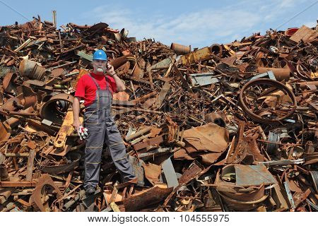 Recycling industry, worker using phone at heap of old metal