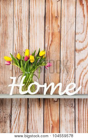 Colorful bouquet tulips in glass vase at home