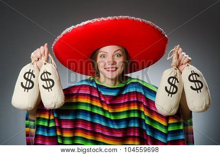 Girl in mexican vivid poncho holding money bags against gray