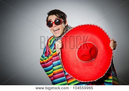 Man in vivid mexican poncho against gray poster