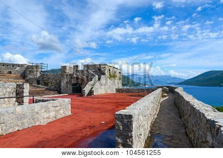 The fortress Kanli Kula (Bloody Tower) on the background of the bay and mountains Herceg Novi Montenegro poster