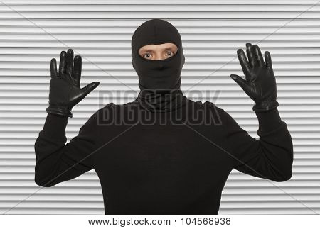 Thief with balaclava caught in front of the wall