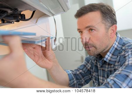 Kitchen fitter installing an extractor fan