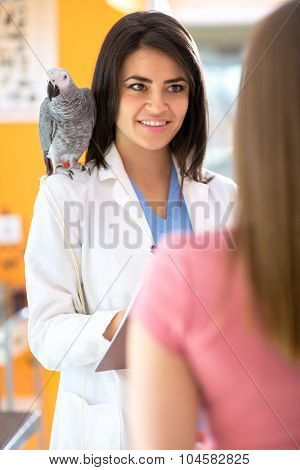 Veterinarian is giving advices to a girl with sick parrot in vet infirmary