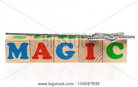MAGIC word formed by wood alphabet blocks with magic wand isolated on white background