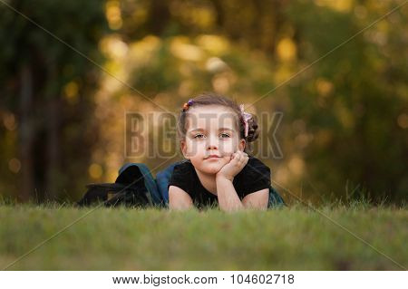 beautiful girl laying on a grass and daydreaming on a nice day in fall