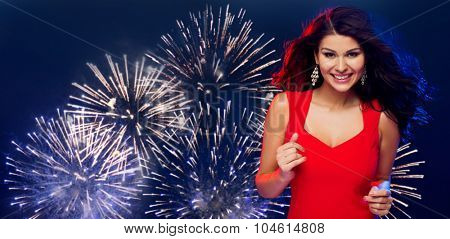 people, holidays, disco, nightlife and leisure concept - beautiful sexy woman in red dress dancing at party over firework in night sky background