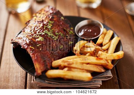 half rack of barbecue pork ribs with french fries on plate with very thing selective focus