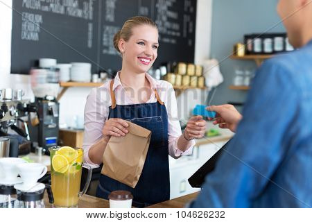 Barista serving customer in coffee shop