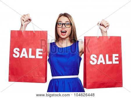 Surprised shopaholic showing red paperbags