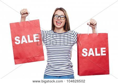 Happy female shopper in eyeglasses holding red paperbags