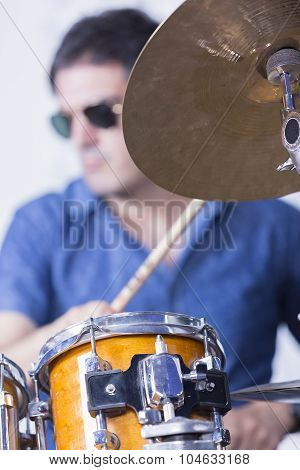 unfocused young male musician is playing set of drums in a recording studio - focus on the top of the drum poster