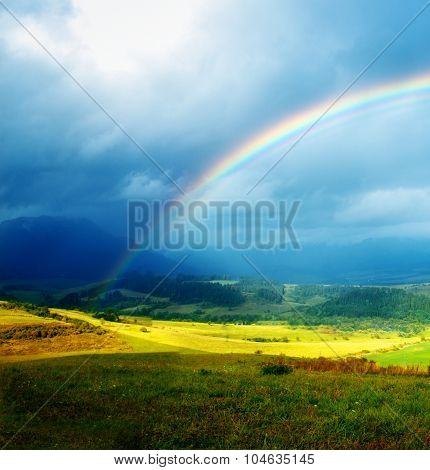 Beautiful landscape, green and yellow meadow and lake with mountain on background with a rainbow in