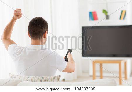 leisure, technology, mass media and people concept - man watching tv and supporting team at home from back