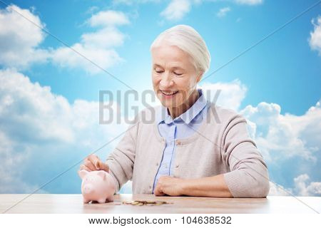 savings, money, annuity insurance, retirement and people concept - smiling senior woman putting coins into piggy bank over blue sky and clouds background
