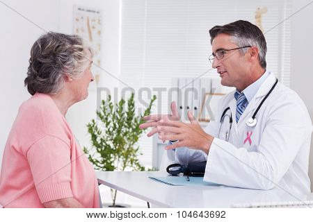 Pink awareness ribbon against male doctor conversing with female patient at table