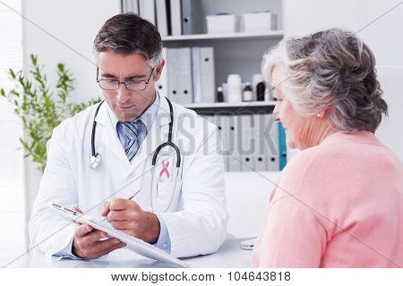 Pink awareness ribbon against doctor explaining prescriptions to senior woman