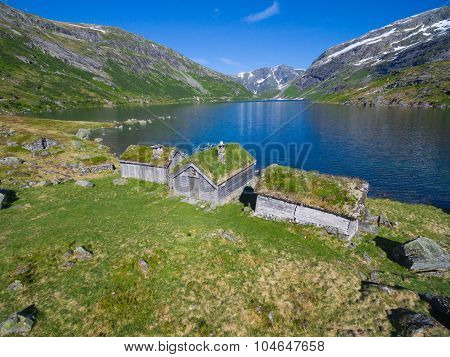Aerial view of old norwegian huts by picturesque lake surrounded by mountains in Gaularfjellet mountain pass in Norway poster