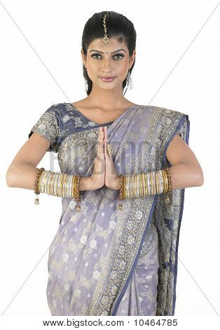 Woman in fancy sari in a greetings expression