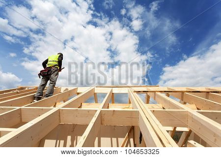 Construction crew working on the roof against blue sky