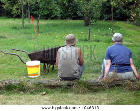Man And Woman/Gardeners Sitting In Garden/Having Break