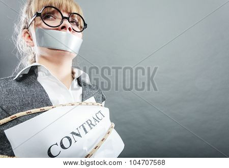 Afraid businesswoman bound by contract terms and conditions with mouth taped shut. Scared woman tied to chair become slave. Business and law concept. poster
