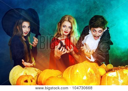 Children at the Halloween party. Traditional costumes and pumpkins decoration. Autumn holidays.