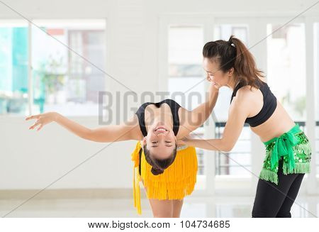 Image of a girl training belly dances with her instructor in the dance hall poster