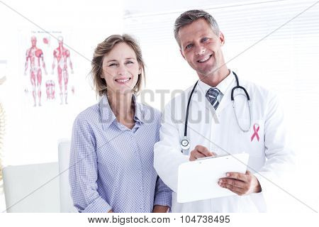 Pink awareness ribbon against doctor and patient smiling at camera