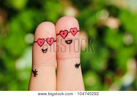 Finger art of a Happy couple. A man and a woman hug in pink glasses in shape of hearts. The concept