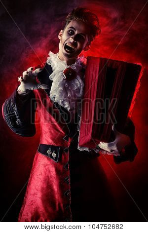Frightening bloodthirsty vampire with a coffin. Halloween. Dracula costume.