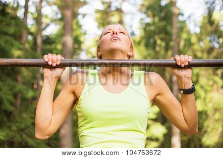 Active and fit woman doing pullups outdoors poster