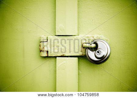 Rusty Padlock On Old Green Painted Wooden Door