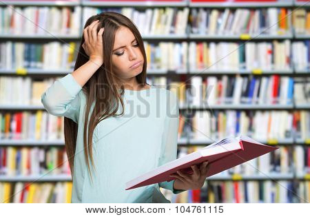 Student with a desperate expression looking at her book