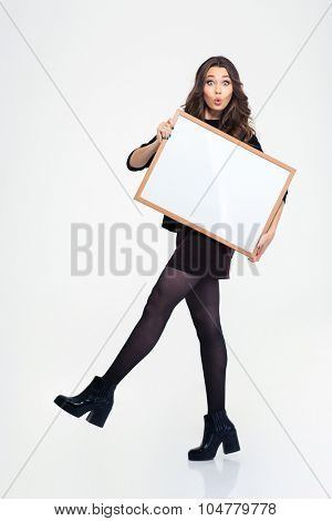 Ful length portrait of a beautiful young girl posing with blank board isolated on a white background