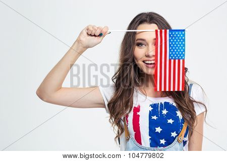 Portrait of a smiling woman covering her eye with USA flag isolated on a white background