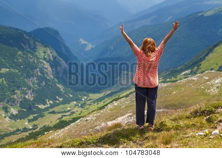 Woman With Raised Hands In Mountains