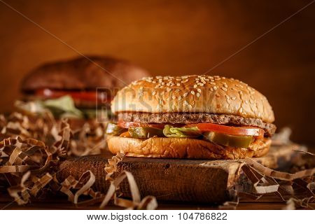 Burger on cutting board on vintage style. Homemade burger or hamburger in dramatic light. Vintage burger or hamburger on old wooden background. Homemade fast food concept. Mouthwatering home made burger. Delicious burger.