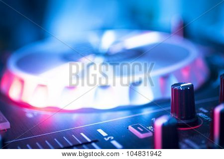 DJ console cd mp4 deejay mixing desk Ibiza house techno dance music wedding reception party in nightclub with colored lighting effect disco lights. poster