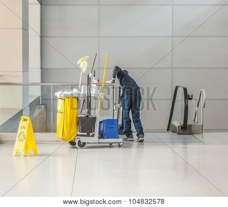 Cleaning Lady With Her Cleaning Trolley Cleans The Glass Of A Staircase In Los Angeles