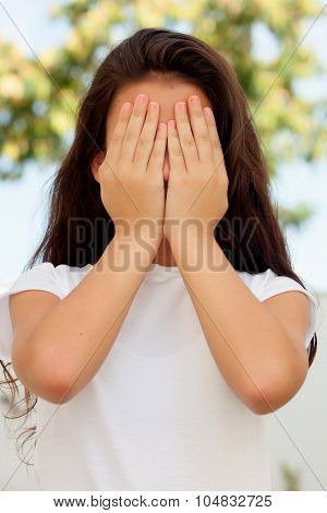 Teenage girl with twelve years old covering her face with the hands