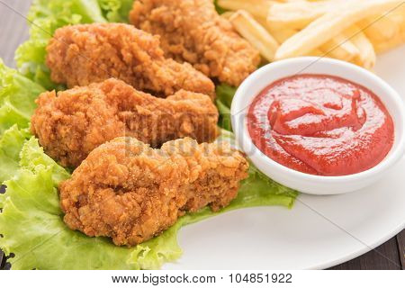 Fried Chicken Drumstick And French Fries On White Dish