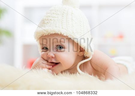 Cute little baby looking into the camera and weared in white hat.